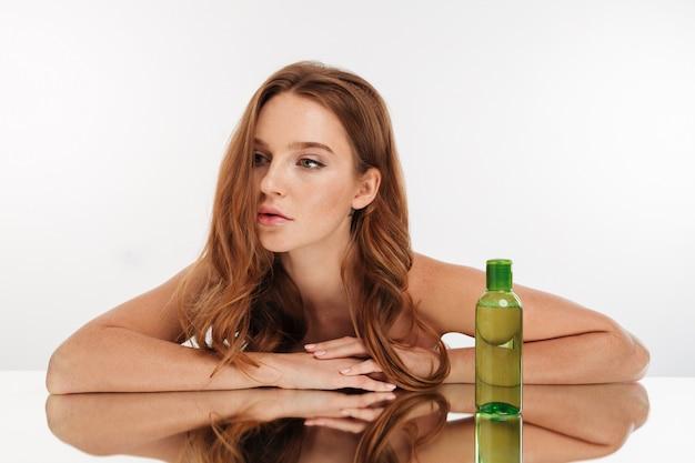 Portrait de beauté de la femme au gingembre féminin aux cheveux longs s'incline sur la table miroir avec une bouteille de lotion
