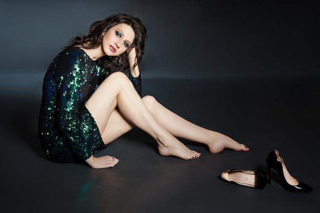 Portrait de beauté d'une femme avec un beau maquillage de soirée assis sur le sol