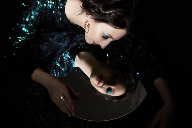 Portrait de beauté d'une femme avec un beau maquillage de soirée et un miroir dans ses mains