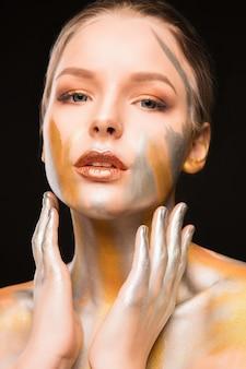 Portrait de beauté d'une femme blonde élégante avec de la peinture dorée et argentée sur ses épaules et son visage