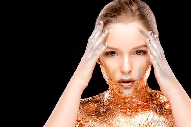 Portrait de beauté d'une femme blonde glamour avec un maquillage créatif et une feuille d'or sur le cou et les épaules. espace pour le texte