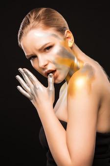 Portrait de beauté d'une femme blonde impressionnante avec de la peinture dorée et argentée sur son cou et son visage