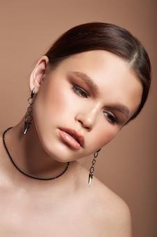Portrait de beauté d'une femme avec des boucles d'oreilles bijoux dans ses oreilles