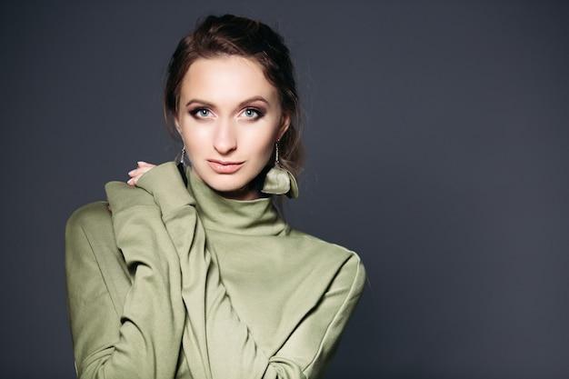 Portrait de beauté d'une femme brune avec des vêtements en robe kaki.