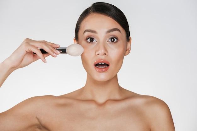 Portrait de beauté de femme excitée avec une peau parfaite regardant la caméra et se maquiller à l'aide d'un pinceau, isolé sur blanc