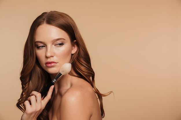 Portrait de beauté de femme gingembre calme aux cheveux longs posant sur le côté tout en regardant en arrière et en tenant la brosse à cosmétiques