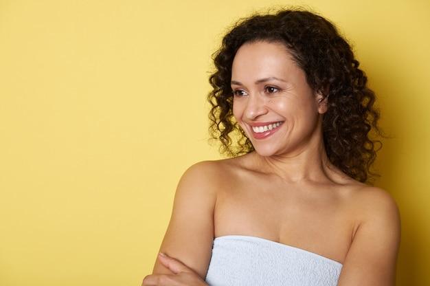 Portrait de beauté d'une femme métisse avec une peau propre et saine sur un mur jaune.