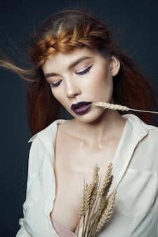Portrait beauté femme avec queue de cochon sur la tête et les épis de blé. rouge à lèvres foncé et maquillage pour les yeux, peau du visage lisse. cheveux flottant dans le vent, blé dans de belles mains femme