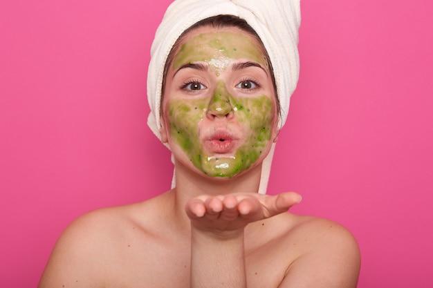 Portrait de beauté de femme de race blanche détendue dans un salon spa avec masque facial vert, portant une serviette blanche