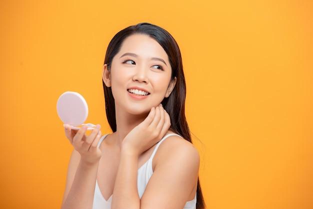 Portrait de beauté d'une femme séduisante joyeuse examinant son visage tout en regardant le miroir isolé sur fond jaune
