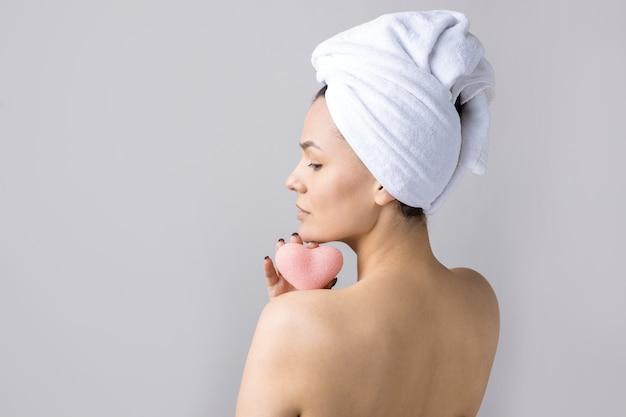 Portrait de beauté de femme en serviette blanche sur la tête avec une éponge pour un corps en vue d'un coeur rose