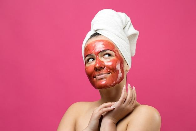 Portrait de beauté d'une femme en serviette blanche sur la tête avec un masque nourrissant doré sur le visage