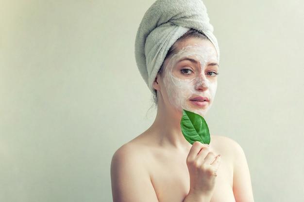 Portrait de beauté de femme en serviette sur la tête avec masque nourrissant blanc ou crème sur le visage et feuille verte à la main, fond blanc isolé. concept de spa cosmétique bio écologique de nettoyage de soins de la peau