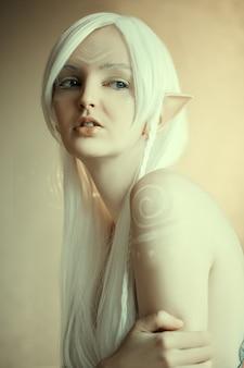 Portrait de beauté d'une fille dans la fantaisie image d'un elfe. cheveux blancs et faceart. longues oreilles elfiques. queue de fée.