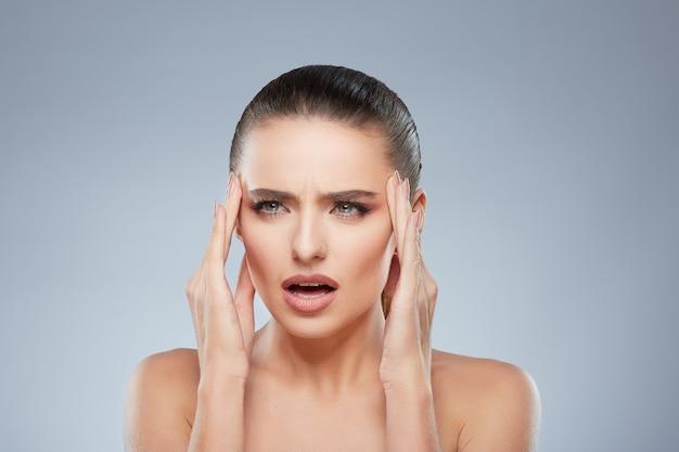 Portrait de beauté de fille fatiguée à côté de douleur. tête et épaules de femme souffrant de maux de tête. maquillage naturel, studio, vraies émotions
