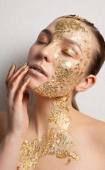 Portrait de beauté d'une fille glamour avec une feuille d'or sur le visage et le cou