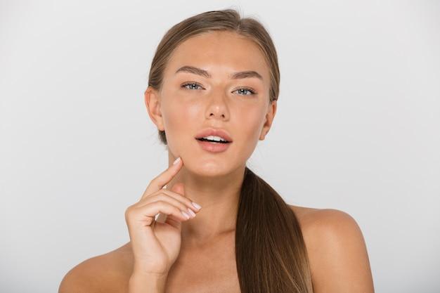 Portrait de beauté d'une fille à moitié nue avec de longs cheveux bruns à la recherche, isolé