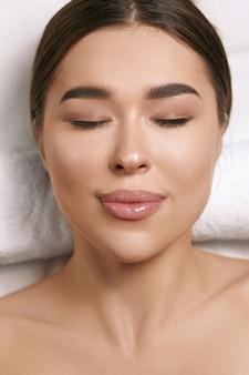 Le portrait de beauté de la fille se trouve sur une table de massage