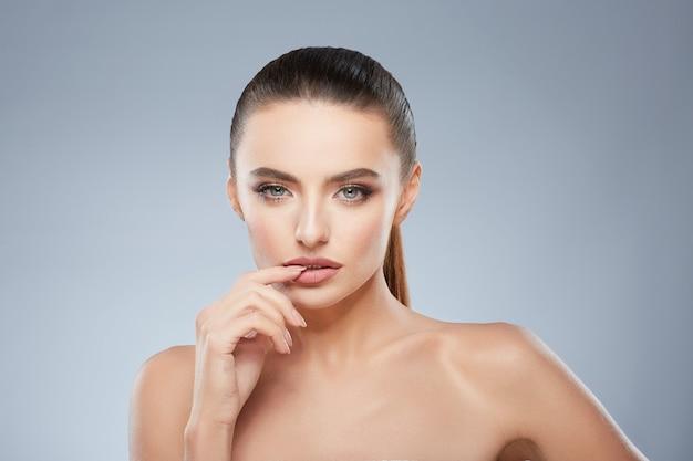 Portrait de beauté de fille séduisante regardant la caméra. tête et épaules de belle femme avec un doigt dans sa bouche. maquillage naturel, studio, vraies émotions