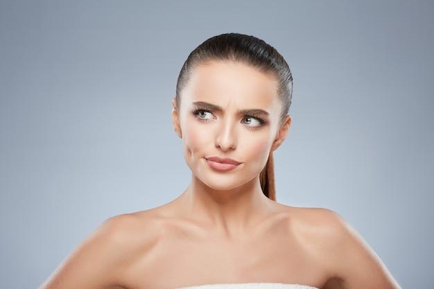 Portrait de beauté d'une fille suspecte à la recherche de côté. tête et épaules de belle femme au visage tendu. maquillage naturel, studio, vraies émotions