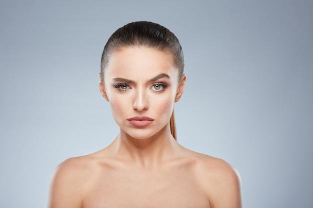 Portrait de beauté d'une fille suspecte regardant la caméra. tête et épaules de belle femme vissant ses yeux. maquillage naturel, studio, vraies émotions