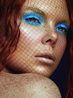 Portrait de beauté d'une jeune femme au maquillage flashy