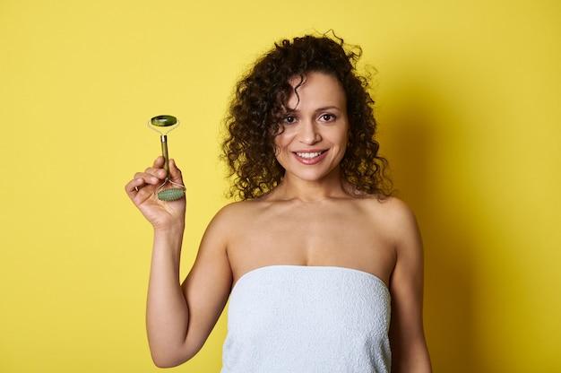 Portrait de beauté de jeune femme aux cheveux bouclés tenant rouleau de jade et souriant sourire à pleines dents posant sur jaune tout avec copie espace