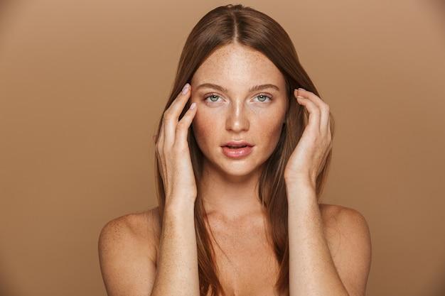 Portrait de beauté d'une jeune femme aux seins nus sensuelle avec de longs cheveux rouges posant, tenant la main sur son visage isolé sur mur beige