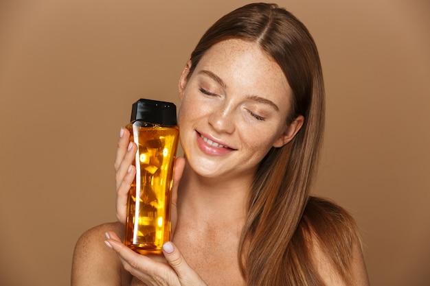 Portrait de beauté d'une jeune femme aux seins nus souriante avec de longs cheveux rouges montrant une bouteille de shampooing isolé sur mur beige