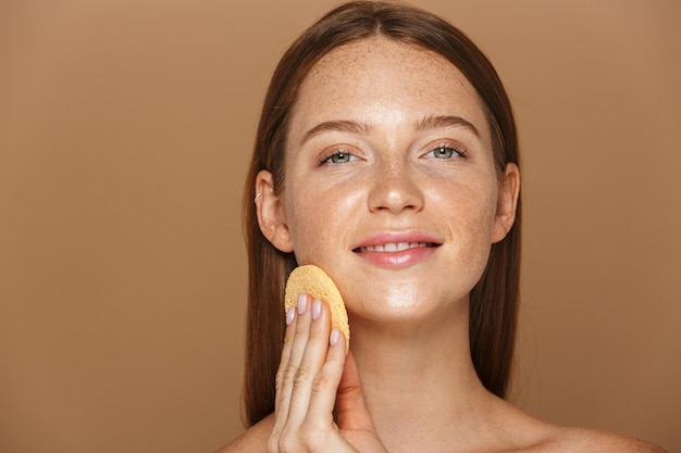Portrait de beauté d'une jeune femme aux seins nus souriante avec de longs cheveux rouges nettoyant son visage avec une éponge isolée sur un mur beige