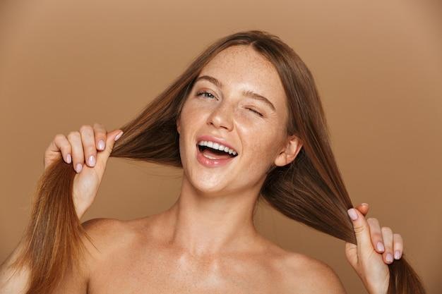 Portrait de beauté d'une jeune femme aux seins nus souriante avec de longs cheveux rouges posant, jouant avec ses cheveux isolés sur mur beige