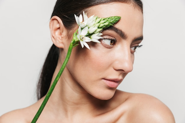 Portrait de beauté d'une jeune femme brune attrayante en bonne santé debout isolé, tenant une fleur sur son visage
