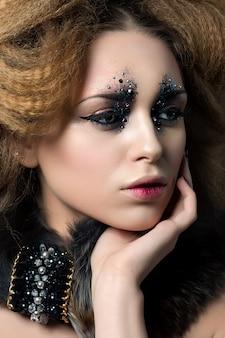 Portrait de beauté de jeune femme avec du maquillage de mode avec des strass touchant son visage .. maquillage de carnaval ou de fête