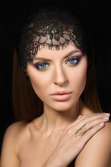 Portrait de beauté de jeune femme avec la main sur son épaule sur fond sombre