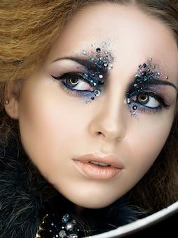 Portrait de beauté de jeune femme avec un maquillage de mode moderne avec des strass. maquillage de carnaval ou de fête