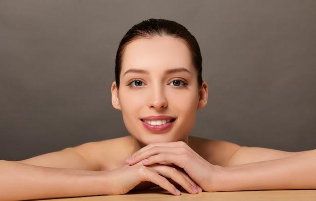 Portrait de beauté d'une jeune femme posant avec ses bras et son visage sur la surface sur fond marron clair