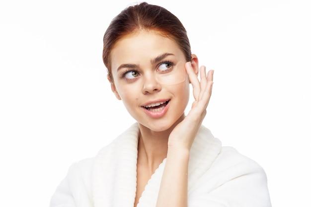 Portrait de beauté d'une jeune femme en robe de chambre sur fond blanc prend soin de la peau du