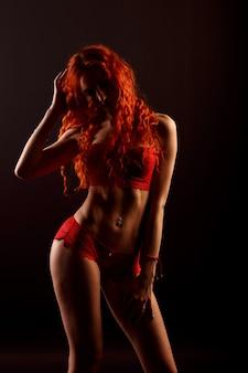 Portrait de beauté jeune femme rousse intime en lingerie sur fond noir.