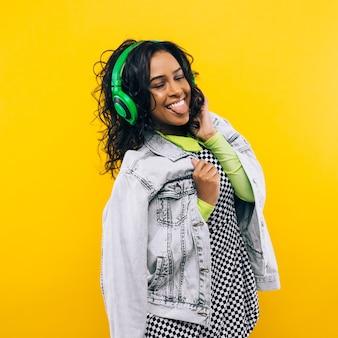 Portrait de beauté de jeune fille afro-américaine avec une coiffure afro. fille posant sur fond jaune, regardant la caméra, souriant. prise de vue en studio.