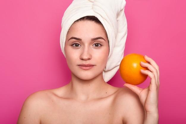 Portrait de beauté de la jeune fille aux épaules nacked. lady détient l'orange, a une expression faciale calme. charmante femme avec une serviette enroulée autour de la tête se détend dans le salon spa. modèle pose en studio photo.