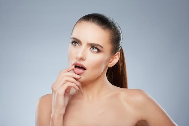 Portrait de beauté de jeune fille à côté de penser à quelque chose. tête et épaules de femme contemplée touchant sa lèvre inférieure. maquillage naturel, studio, vraies émotions