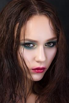 Portrait de beauté de jeune fille avec du maquillage de mode. yeux charbonneux verts et or et lèvres rouges avec contour flou