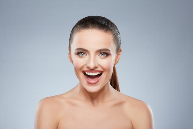 Portrait de beauté d'une jeune fille souriante heureuse regardant la caméra. tête et épaules de belle femme joyeuse avec un large sourire. maquillage naturel, studio, vraies émotions