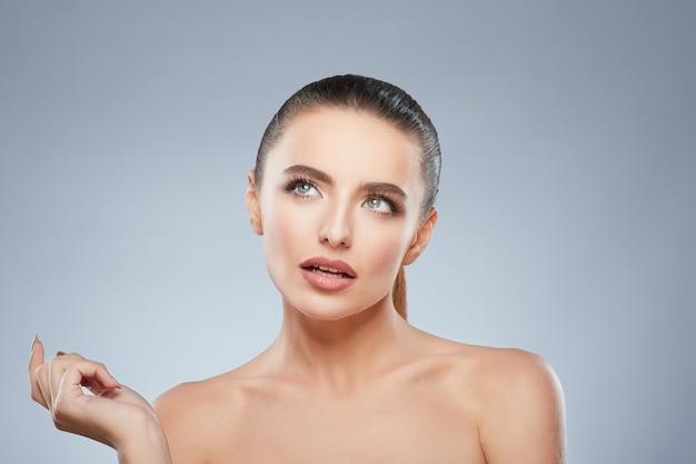 Portrait de beauté de jeune fille en train de penser à quelque chose. tête et épaules de femme contemplée. maquillage naturel, studio, vraies émotions