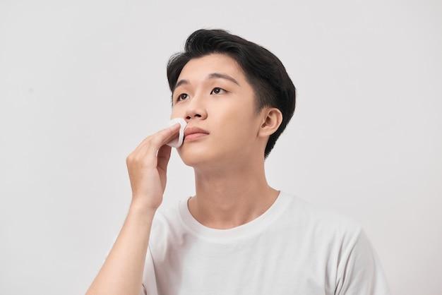 Portrait de beauté d'un jeune homme confiant à l'aide d'un coton sur son visage isolé sur fond blanc
