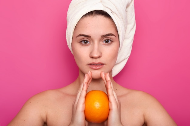 Portrait de beauté de jeune jolie femme à moitié nue avec une serviette blanche enroulée autour de sa tête, tient l'orange à la main. beauté, concept de soins de la peau.