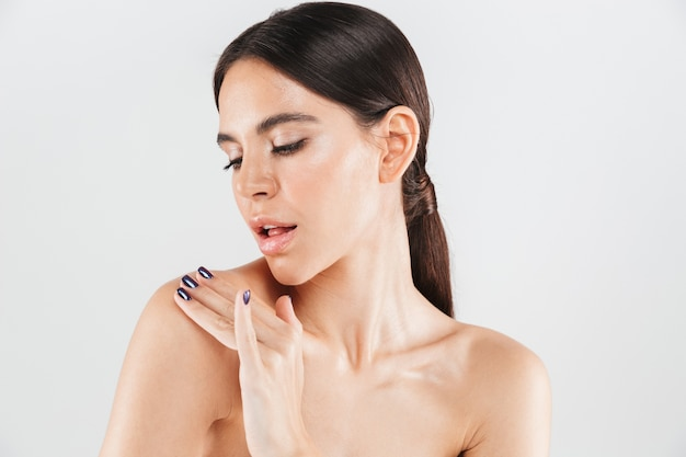 Portrait de beauté d'une jolie femme en bonne santé debout isolé sur un mur blanc, appliquant une crème hydratante sur son épaule