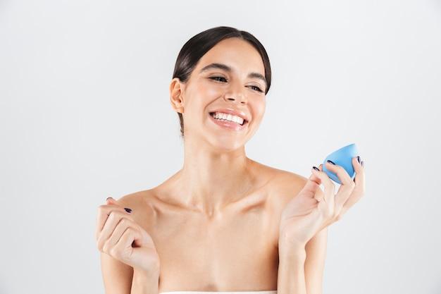 Portrait de beauté d'une jolie femme en bonne santé debout isolé sur un mur blanc, montrant une éponge de maquillage