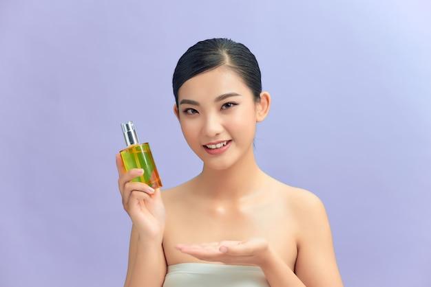 Portrait de beauté d'une jolie femme brune seins nus en bonne santé isolée sur fond violet, montrant une bouteille cosmétique