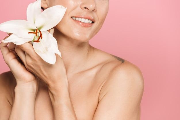 Portrait de beauté d'une jolie femme brune sensuelle souriante aux seins nus debout isolée, posant avec une fleur de lys